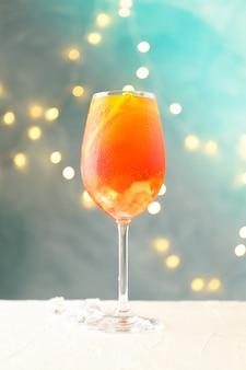 Zusammensetzung mit aperol spritz cocktail und verschwommenen lichtern