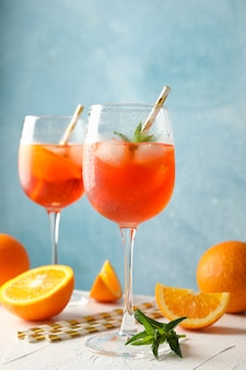 Zusammensetzung mit aperol-spritz-cocktail vor blauem hintergrund