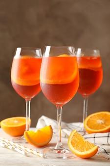 Zusammensetzung mit aperol-spritz-cocktail vor braunem hintergrund