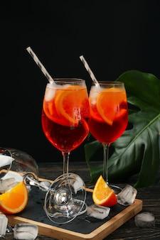 Zusammensetzung mit aperol-spritz-cocktail vor schwarzem hintergrund