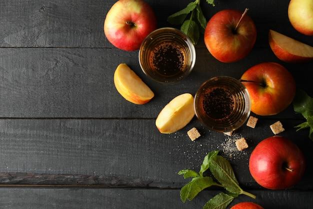 Zusammensetzung mit apfelwein, zucker und äpfeln auf holztisch