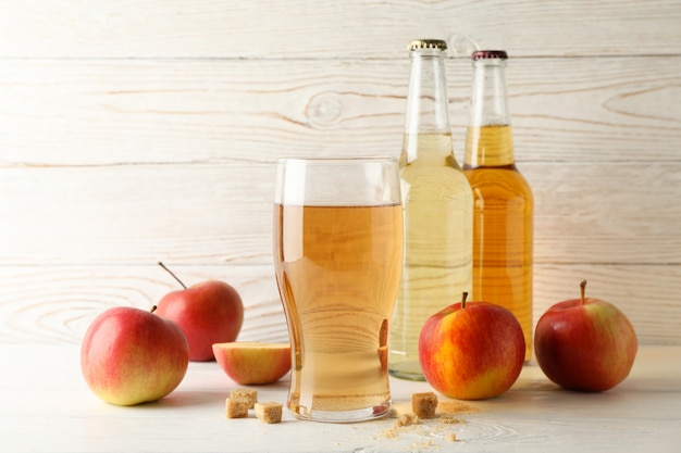 Zusammensetzung mit apfelwein, zucker und äpfeln auf weißem holztisch