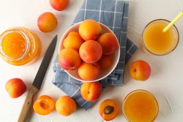 Zusammensetzung mit aprikosen, saft und marmelade auf weißem tisch
