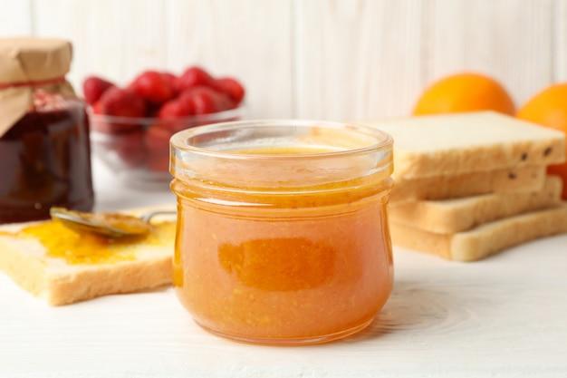 Zusammensetzung mit aprikosenmarmelade auf weißem holz. süßes frühstück