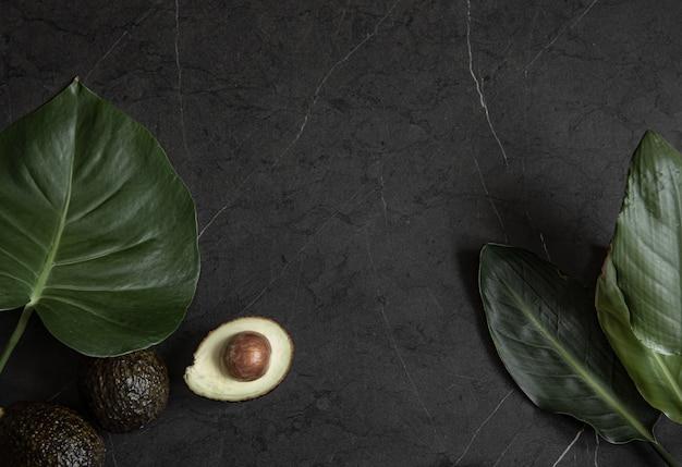 Zusammensetzung mit avocado und tropischen blättern auf einer schwarzen marmoroberfläche draufsicht.