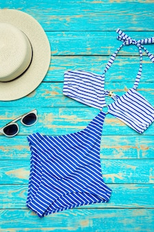 Zusammensetzung mit badeanzug auf farbhölzernem hintergrund