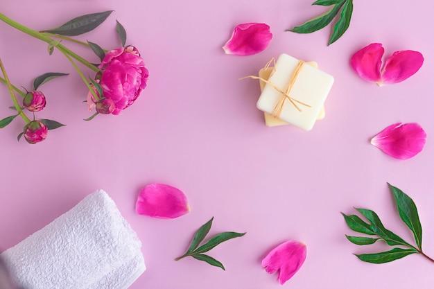 Zusammensetzung mit blumen, blütenblättern der pfingstrose, natürlicher bio-seife und handtuch. schönheits-, hautpflegekonzept. flache lage, draufsicht