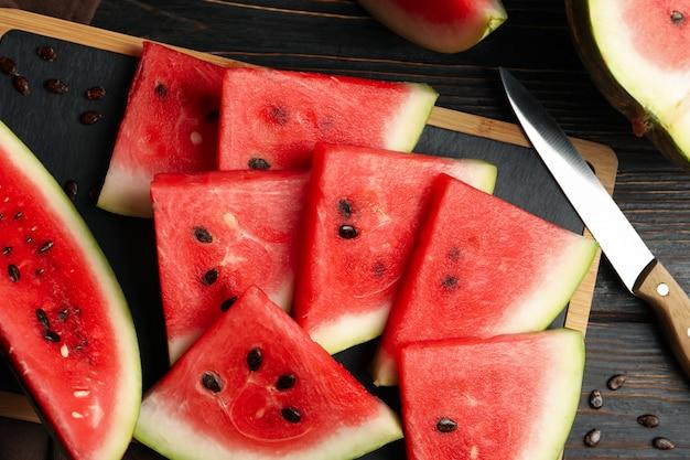 Zusammensetzung mit brett mit wassermelonenscheiben auf holztisch