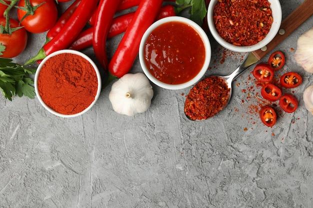 Zusammensetzung mit chili-pfeffer, pulvergewürz, knoblauch und sauce auf grauer wand