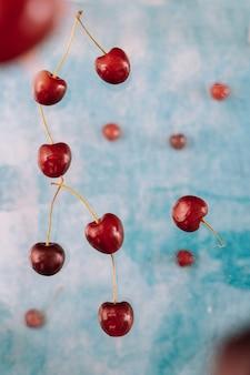 Zusammensetzung mit dem fliegen von süßen roten beeren über levitation auf blauem hintergrund. schwebendes essen, schwebende beeren