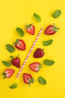 Zusammensetzung mit einem cocktailstrohhalm, erdbeeren und minze. draufsicht.