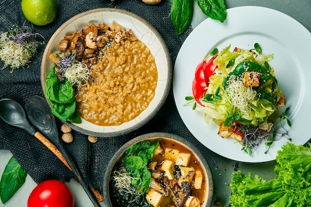 Zusammensetzung mit einem esstisch mit vegetarischen gerichten: risotto mit pilzen, frischem salat und misosuppe auf einem grauen tuch. gesundes und ausgewogenes essen. menüfoto, draufsicht