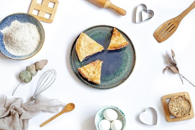 Zusammensetzung mit einem stück kuchen auf einem teller und zutaten zum kochen und küchenzubehör auf weißem tisch.