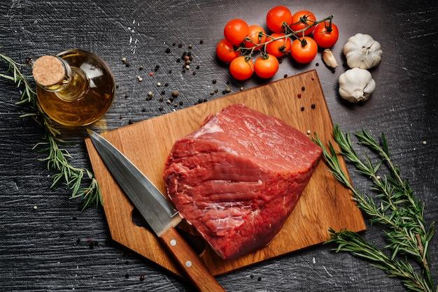 Zusammensetzung mit einem stück rohem rindfleisch, kirschsubmidoren, rosmarinzweigen, knoblauch und olivenöl.