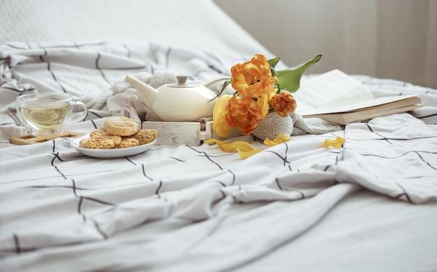 Zusammensetzung mit einer tasse tee, einer teekanne, einem strauß tulpen und kekse im bett