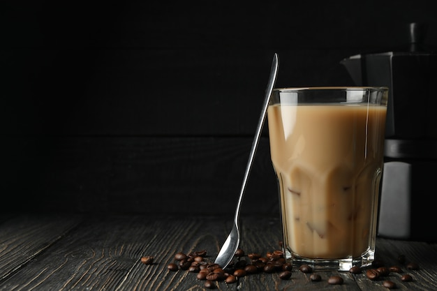 Zusammensetzung mit eiskaffee und kaffeesamen auf hölzernem hintergrund