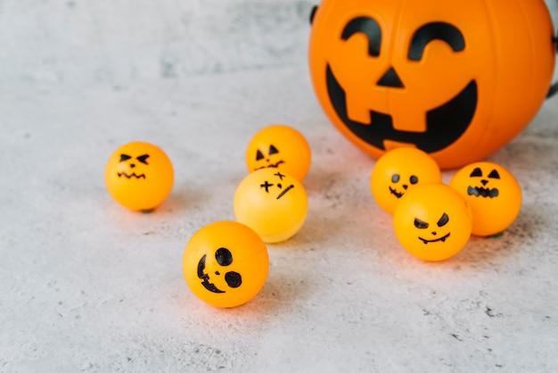 Zusammensetzung mit halloween-kürbiskorb und kleinen orange kugeln