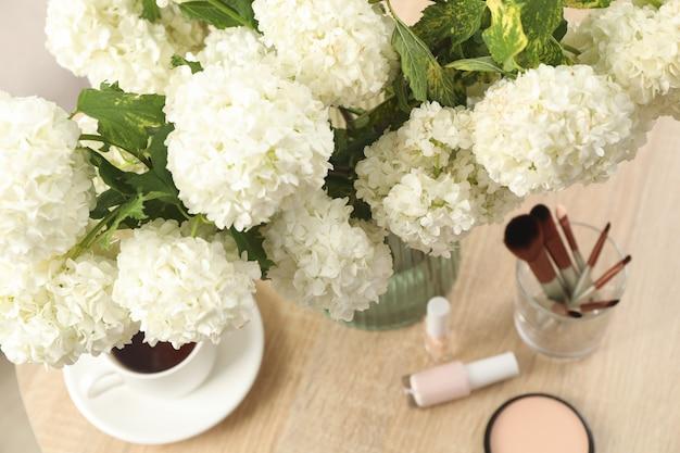 Zusammensetzung mit hortensienblüten, einer tasse kaffee und kosmetika. frühlingspflanze