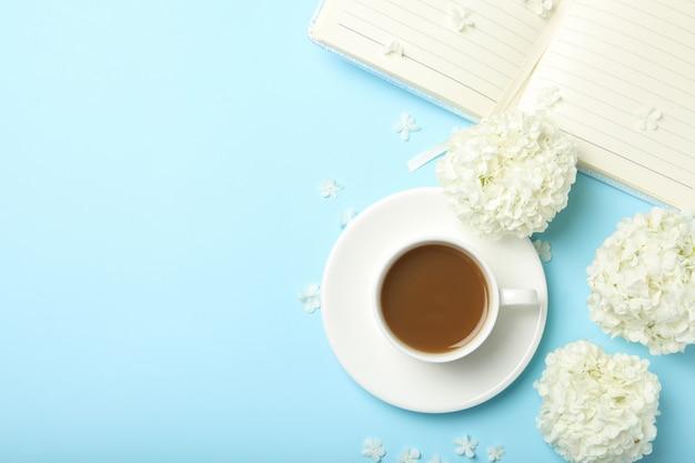 Zusammensetzung mit hortensienblumen und kaffee auf blauem raum