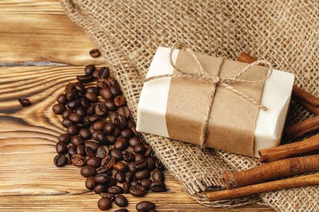 Zusammensetzung mit kaffeekörnern, seife auf dem holztisch, nahaufnahme