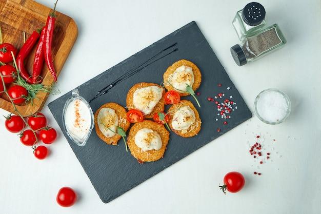Zusammensetzung mit kartoffelpuffer mit saurer sahne auf einem schwarzen steinbrett auf einem weißen tisch.