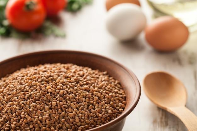 Zusammensetzung mit keramischer schüssel trockener buchweizen, eier und tomaten.