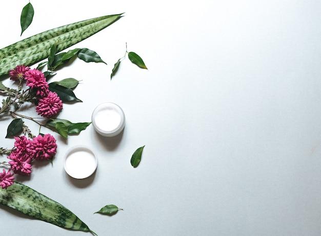 . zusammensetzung mit körperpflegeprodukten, bündel und grünem blatt auf weißem hintergrund, draufsicht, flache lage.