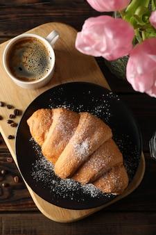 Zusammensetzung mit köstlichem croissant auf hölzernem hintergrund, draufsicht