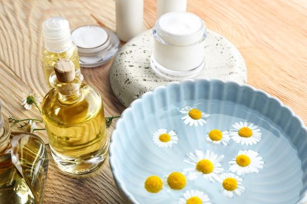 Zusammensetzung mit kosmetischen produkten und frischen kamillenblüten auf holztisch