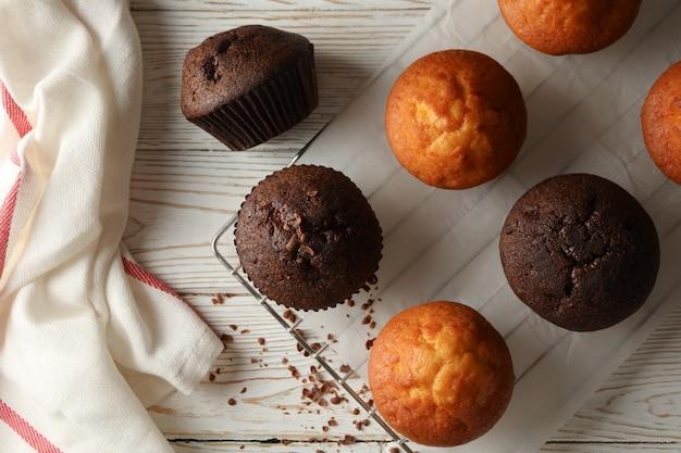 Zusammensetzung mit leckeren muffins auf weißem holzhintergrund
