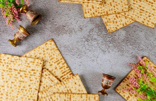 Zusammensetzung mit matzebrot, weinbechern und blumen. draufsicht. pessach jüdischer feiertag.