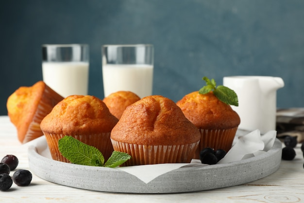 Zusammensetzung mit muffins und milch auf weißem hölzernem hintergrund