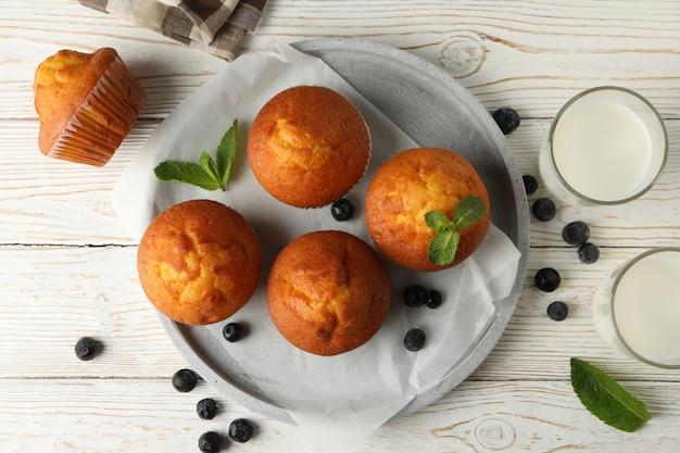 Zusammensetzung mit muffins und milch auf weißem holz