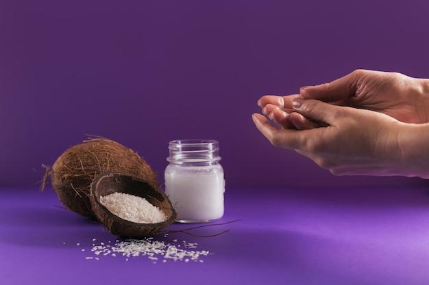 Zusammensetzung mit natürlicher kosmetischer körpercreme des organischen kokosnussöls auf purpurfarbenem hintergrund