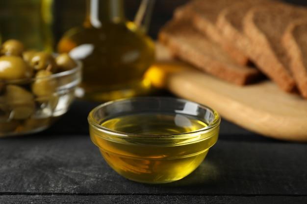 Zusammensetzung mit olivenöl, brot und oliven auf holz, nahaufnahme