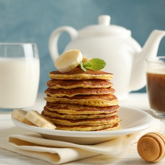 Zusammensetzung mit pfannkuchen, milch und kakaogetränk auf holztisch. süßes frühstück