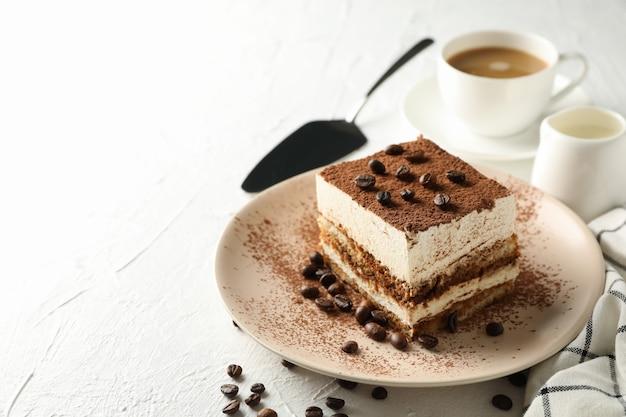 Zusammensetzung mit platte des leckeren tiramisu auf weißem hintergrund. leckeres dessert
