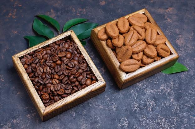Zusammensetzung mit röstkaffeebohnen und kaffeebohne formte plätzchen auf dunkelbrauner oberfläche