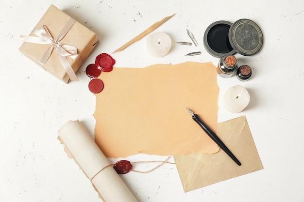 Zusammensetzung mit schreibfederhalter, papierblatt und tintenfass auf dem tisch
