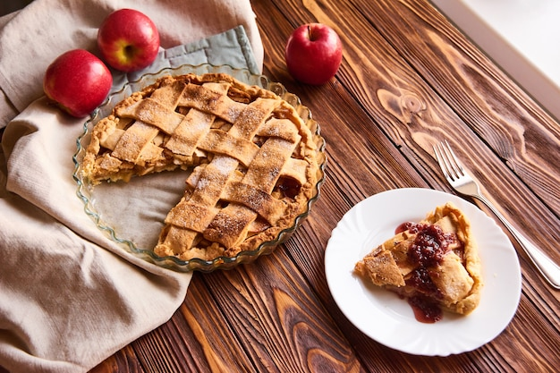 Zusammensetzung mit selbst gemachtem geschmackvollem apfelkuchen auf holztisch. äpfel. leinen handtuch.