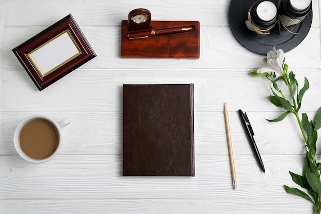 Zusammensetzung mit stationärer notizbuchstift-bleistiftkaffee-blumenebenenlage der bürobildung