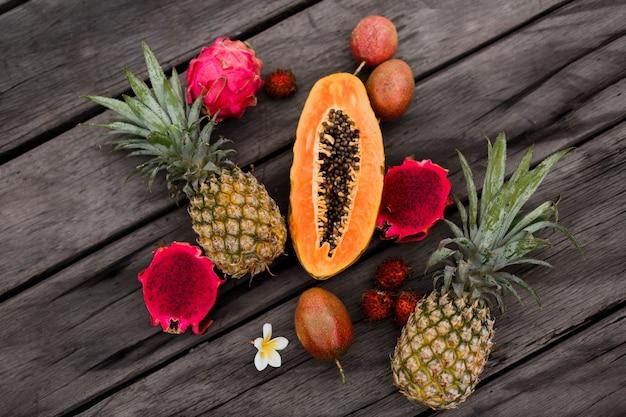 Zusammensetzung mit tropischen früchten auf holzoberfläche