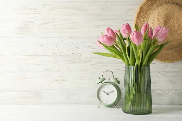 Zusammensetzung mit tulpen in der vase auf hölzernem hintergrund, nahaufnahme
