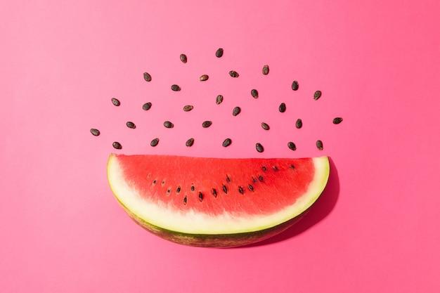 Zusammensetzung mit wassermelonenscheibe auf rosa raum. sommerfrucht