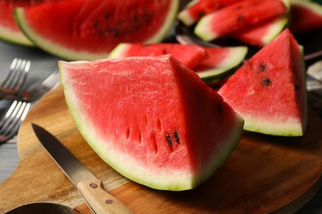 Zusammensetzung mit wassermelonenscheiben auf grauem holztisch. sommerfrucht