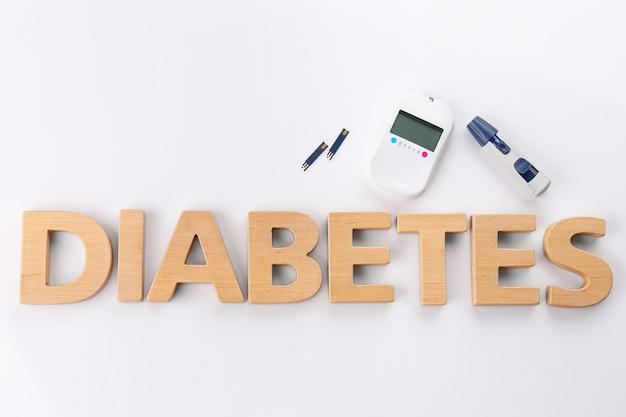 Zusammensetzung mit wort diabetes und glukometer auf weiß