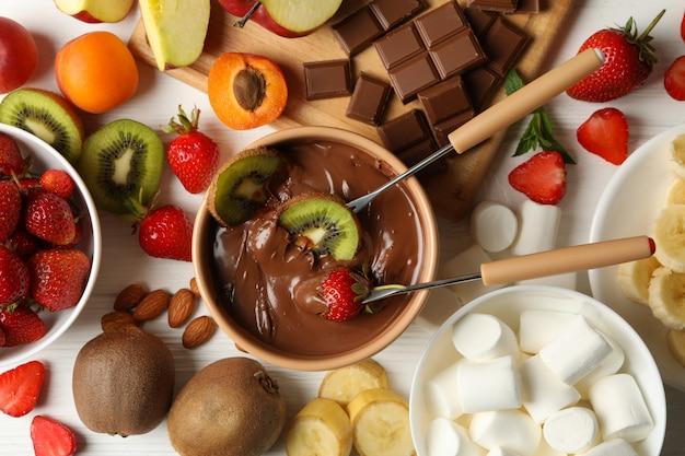 Zusammensetzung mit zutaten für schokoladenfondue auf weißem holzhintergrund. fondue kochen