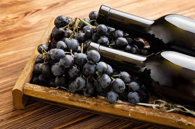 Zusammensetzung mit zwei rotweinflaschen auf braunem holztisch. rotweinflaschen im kasten auf schwarzen reifen trauben auf holztisch. alter sammlungswein.