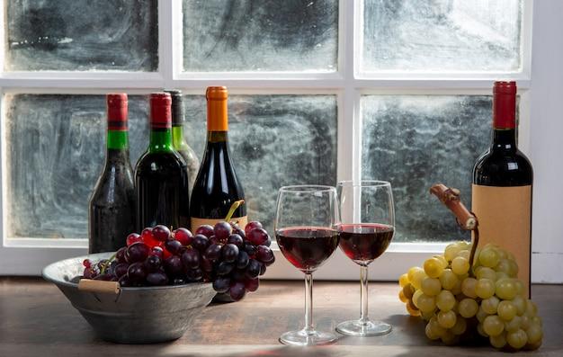 Zusammensetzung mit zwei weingläsern, trauben und flaschen rotwein