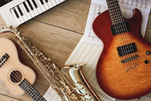 Zusammensetzung verschiedener musikinstrumente: synthesizer, e-gitarre, saxophon und ukulele liegend, blätter mit musiknoten liegend und holzboden. musikinstrumente. musikequipment